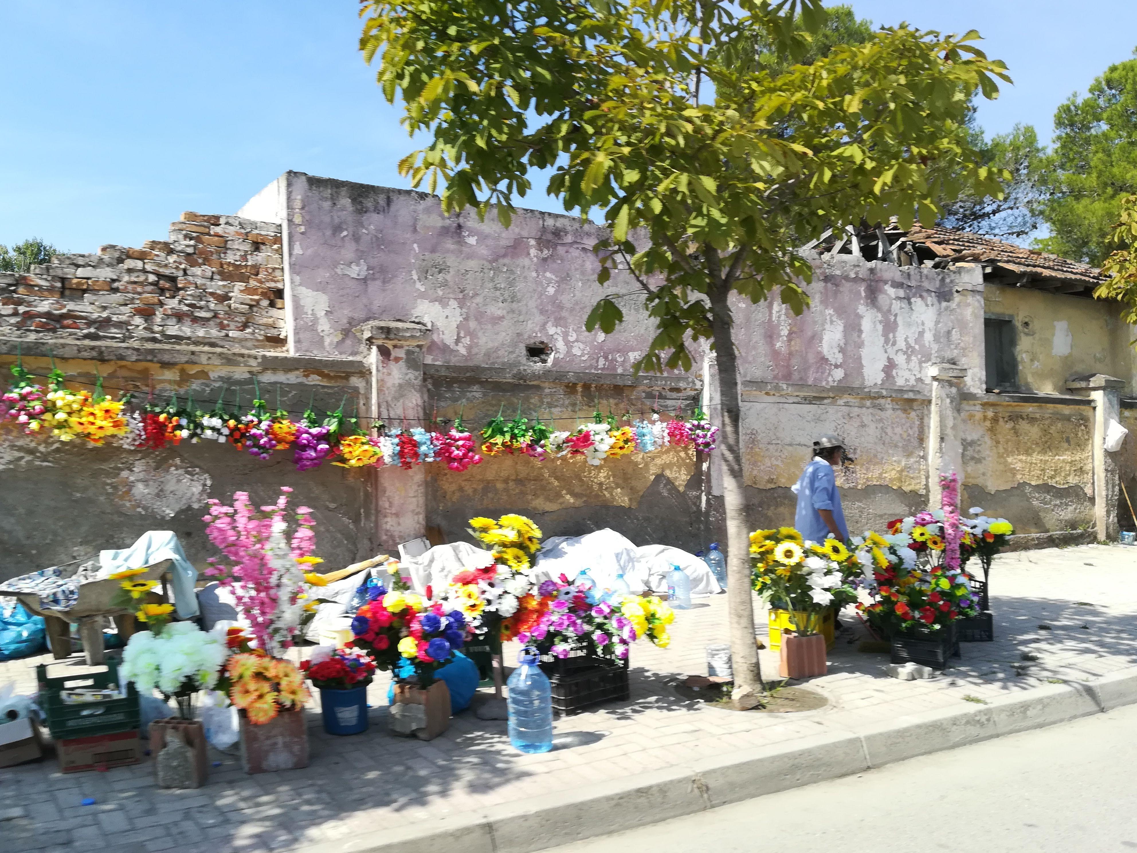 """<img src=""""/blumenstand-in-albanien.jpg"""" alt=""""Ein Blumenstand vor dem Friedhof in Durres"""">"""